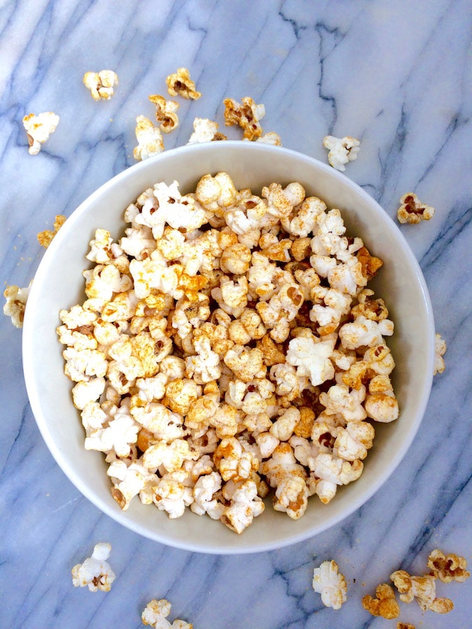 A bowl of healthy turmeric popcorn that's superfood-ified with colorful turmeric.