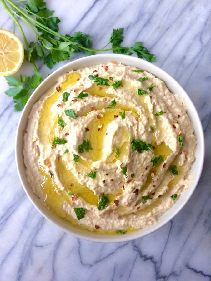 An overhead shot of a bowl of homemade hummus, drizzled with olive oil and sprinkled with parsley.