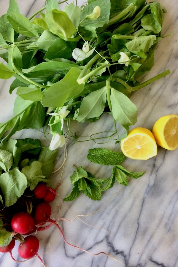 A bunch of pea shoots, a bunch of radishes, some mint leaves, and a sliced lemon.