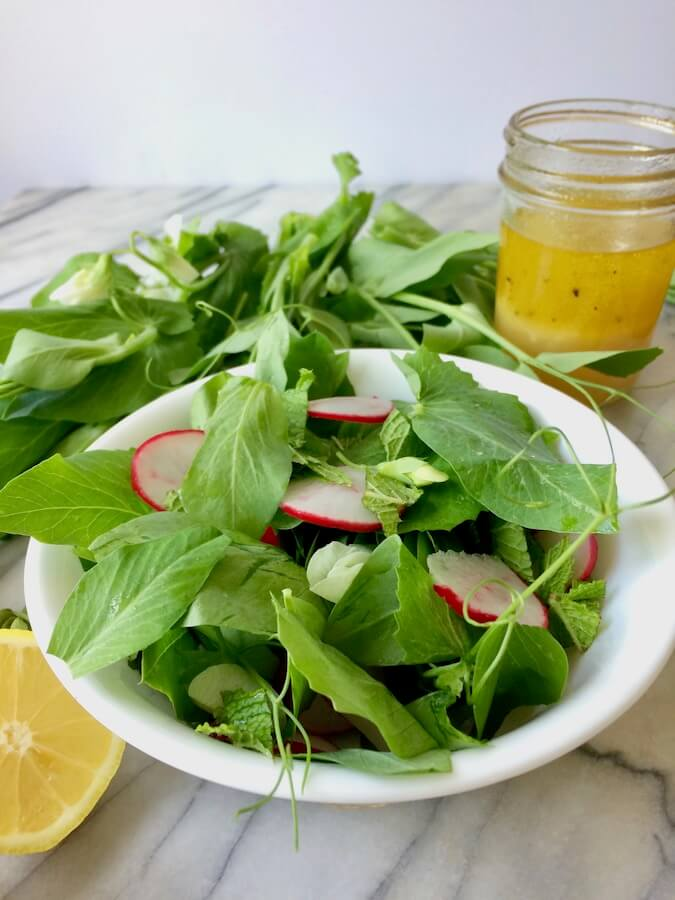 A bowl of pea shoot salad, with mint and radishes, and a jar of lemon-garlic dressing.