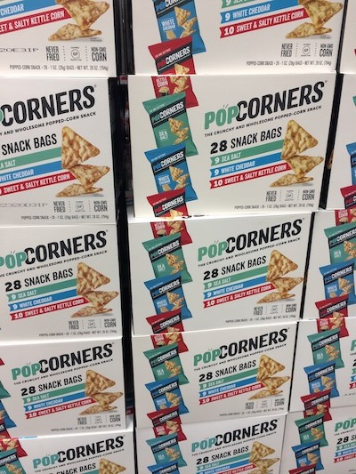Stacks of boxes of Popcorners chips at Costco.